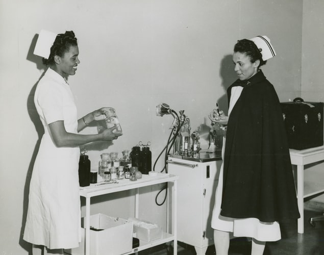 An old black and white photo from the New York Public Library Archives, showing two Black nurses, wearing the old uniform dresses and caps, one with a cape, standing facing one another. They are smiling, as if in conversation, and holding vials for injections.
