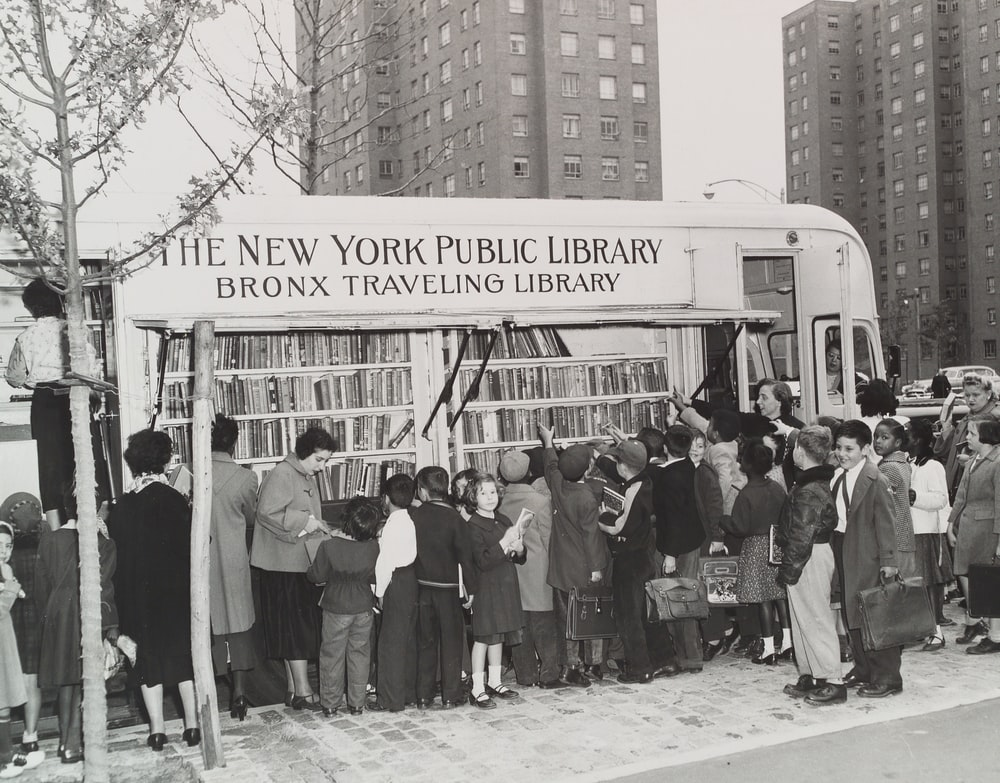 grayscale photo of people standing near the traveling New York Public Library