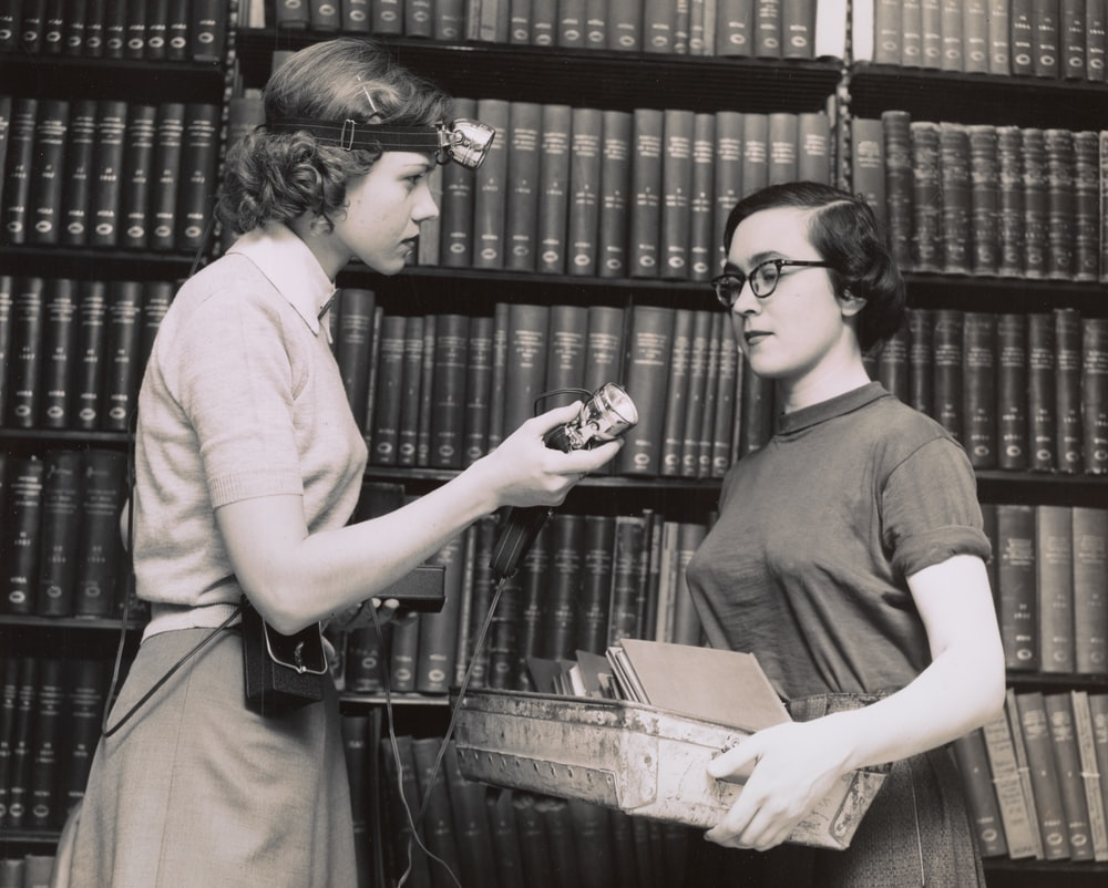 two women talking in the library