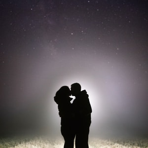 silhouette of man and woman kissing under starry night