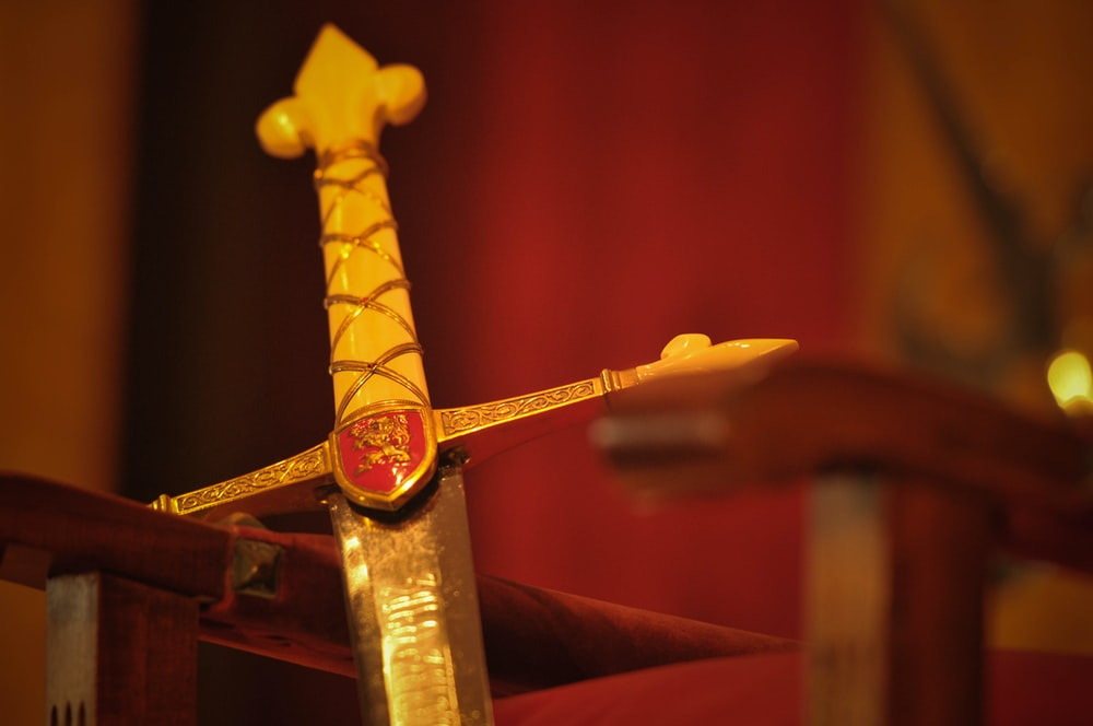 gold sword on red textile