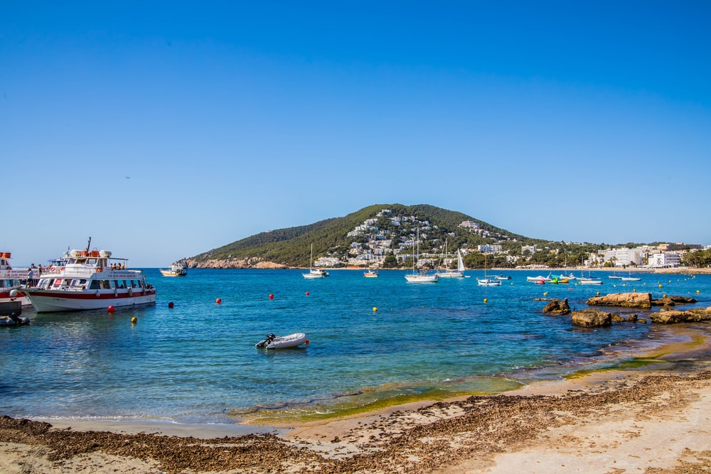 people riding on white boat on sea during daytime, Siesta Hill, Santa Eulalia