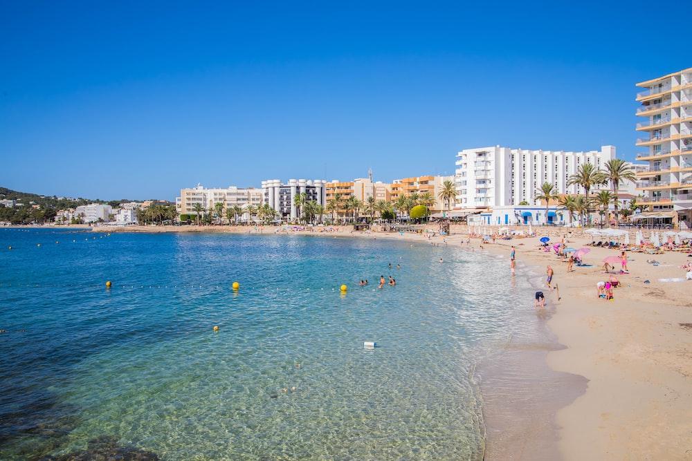people on beach during daytime. Santa Eulalia, Mariners beach, Ibiza with kids