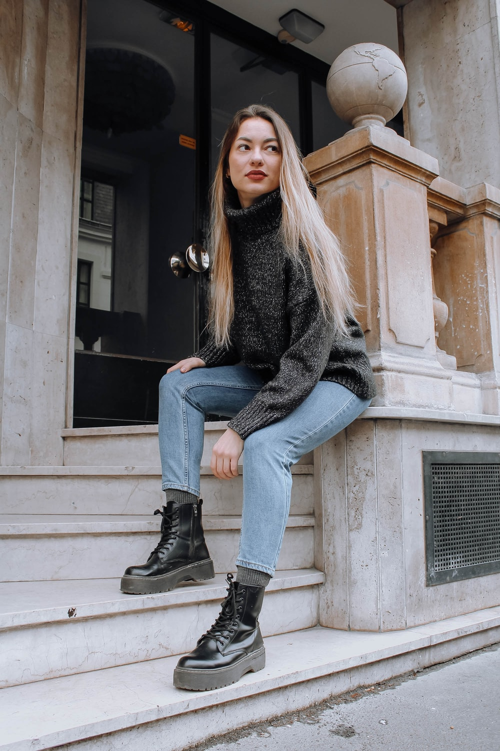 woman in black sweater and blue denim jeans sitting on gray concrete bench