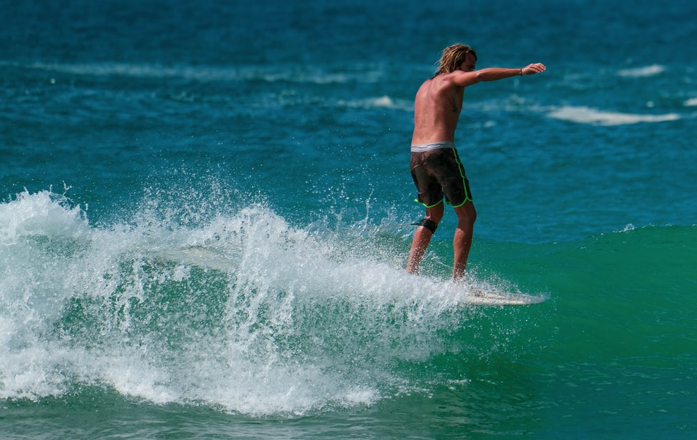 man in black shorts surfing on sea waves during daytime
