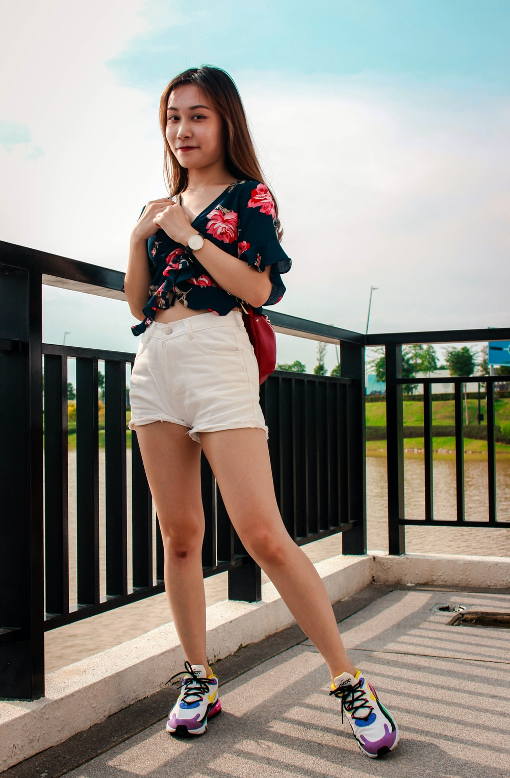 woman in black and red floral shirt and white shorts standing beside black metal fence during