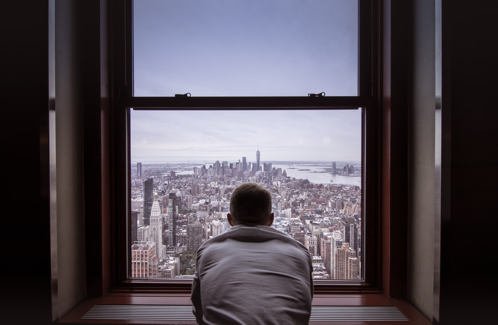 man in gray shirt looking at city buildings during daytime