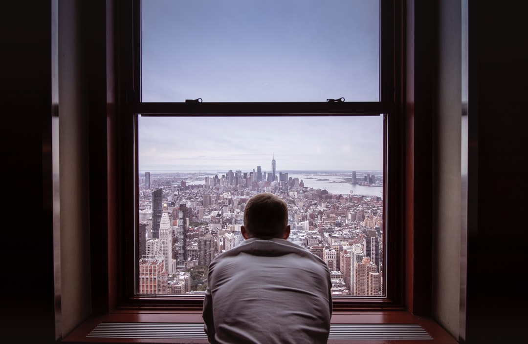 Man In Gray Shirt Looking At City Buildings During Daytime - unsplash