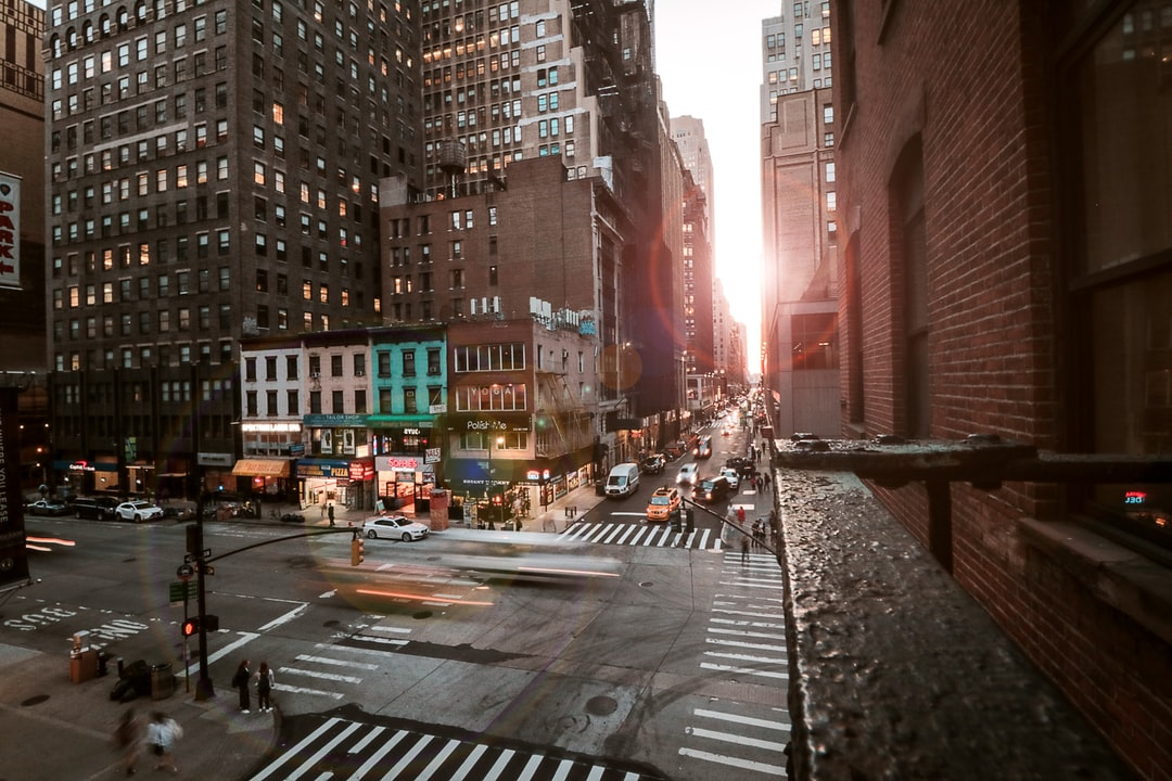 Cars On Road Between High Rise Buildings During Daytime - unsplash