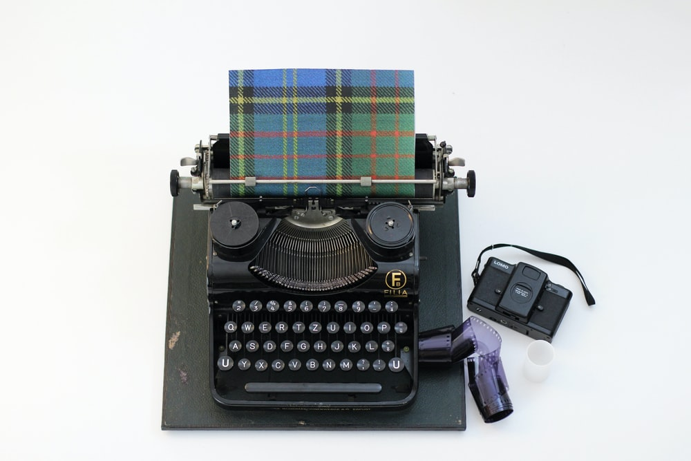 black and green typewriter beside purple and white plastic bottle
