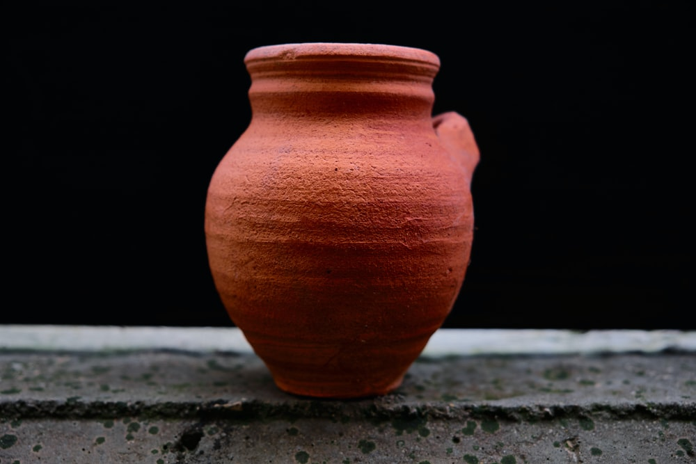 brown clay vase on gray concrete surface