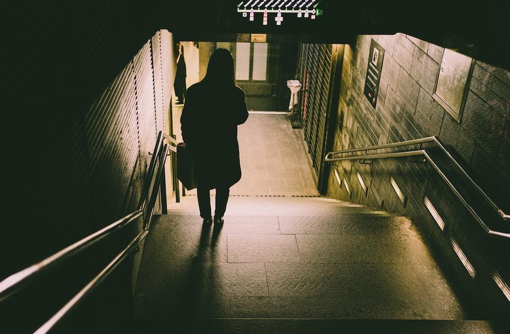 woman in black coat walking on hallway