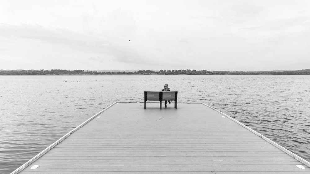 grayscale photo of wooden dock on body of water