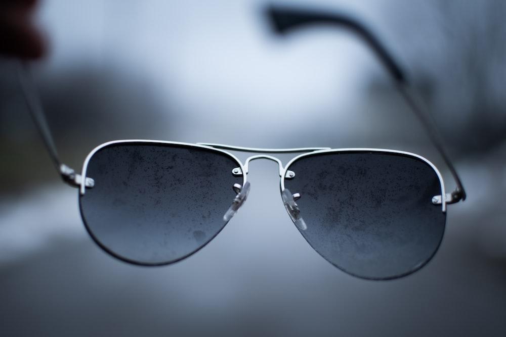 black framed sunglasses on white surface