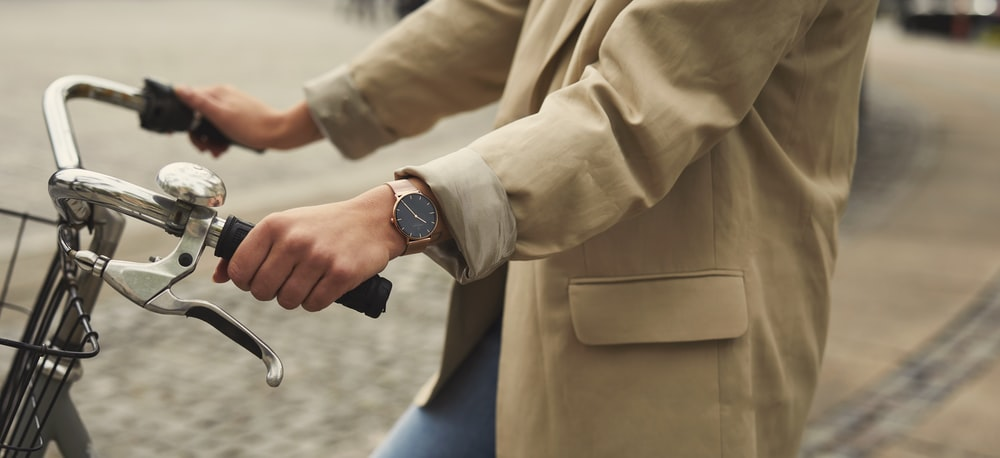 person in brown dress shirt and blue denim jeans wearing silver watch