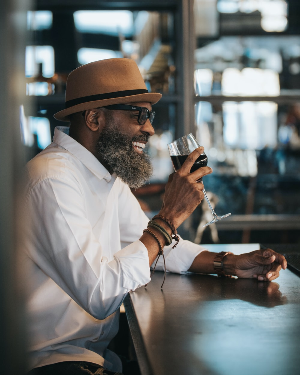 man in white dress shirt and brown hat holding clear drinking glass