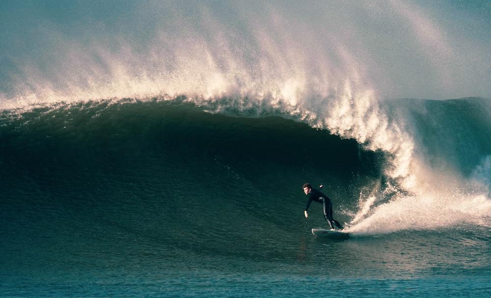man surfing on ocean waves during daytime
