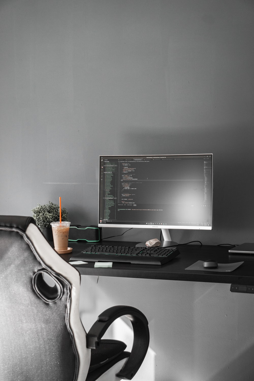 black flat screen computer monitor on black wooden desk
