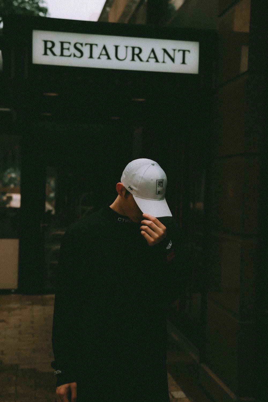man in black long sleeve shirt wearing white cap