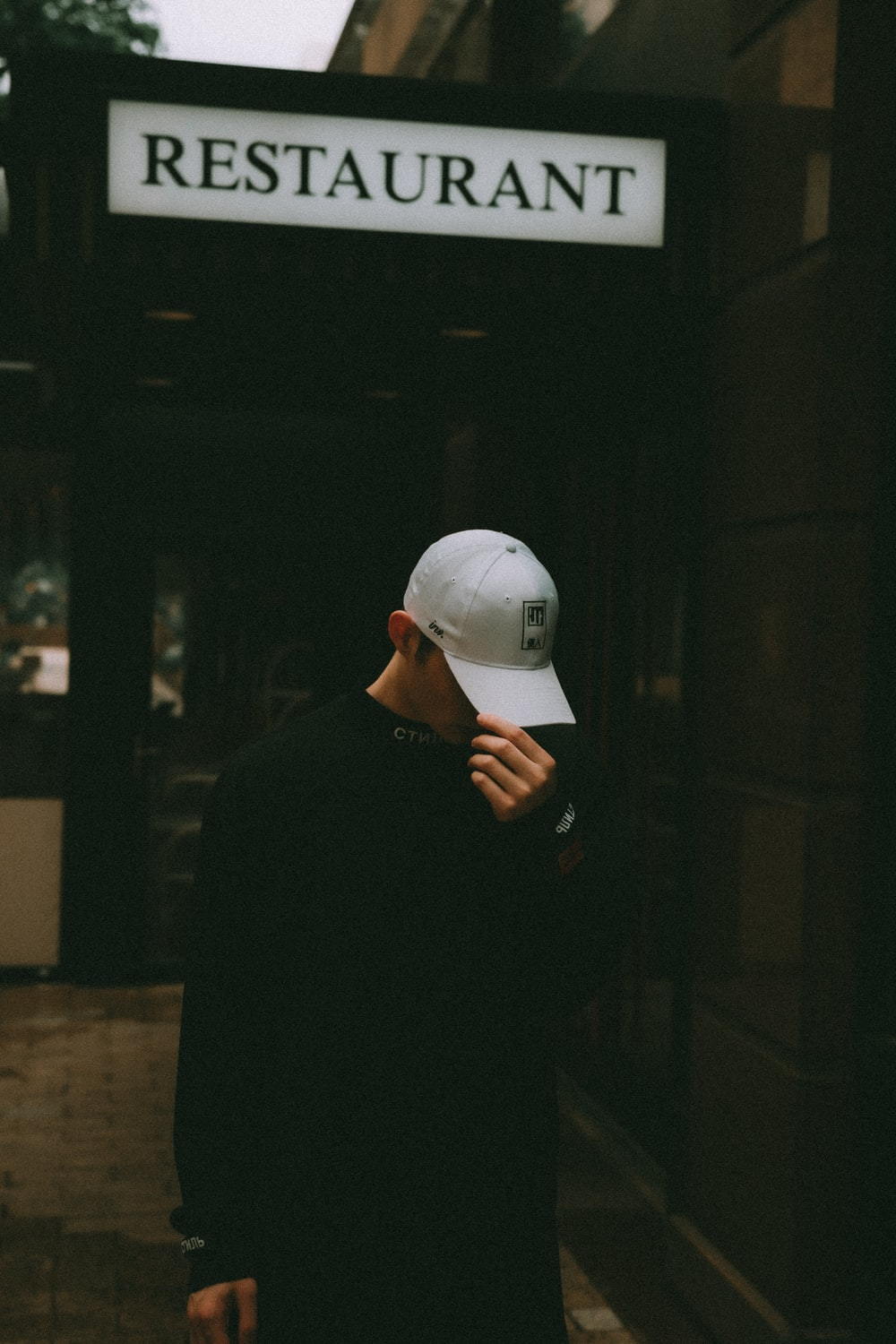 man in black long sleeve shirt wearing white cap