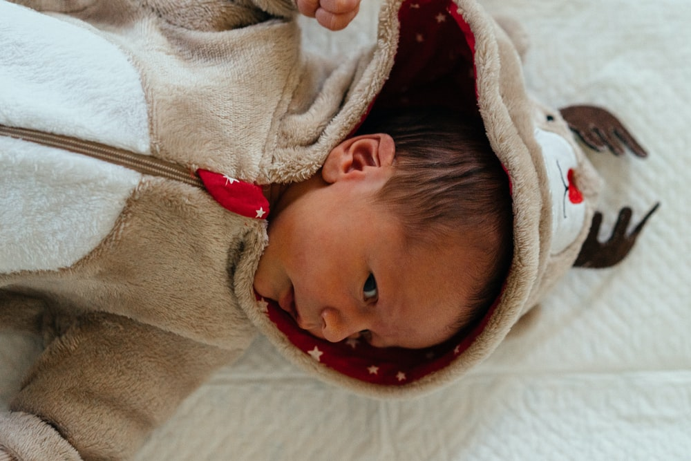 baby in white and red shirt lying on white textile