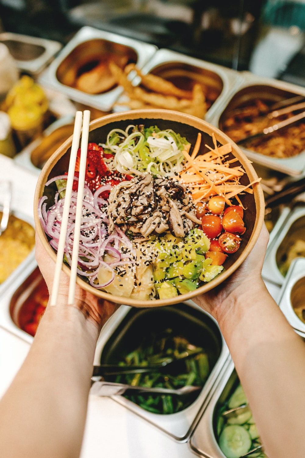 person holding brown wooden chopsticks with green vegetable salad