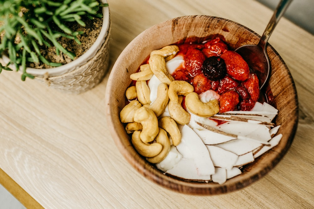 sliced strawberries on brown wooden bowl