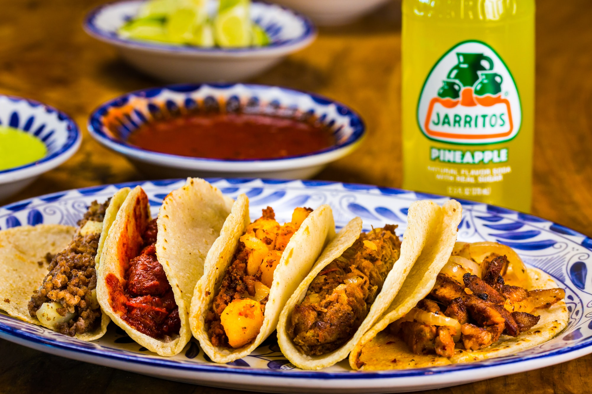 A mixed taco plate served with an all-natural-flavored Jarritos Pineapple Mexican Soda. The dish is served on a traditional Talavera plate.