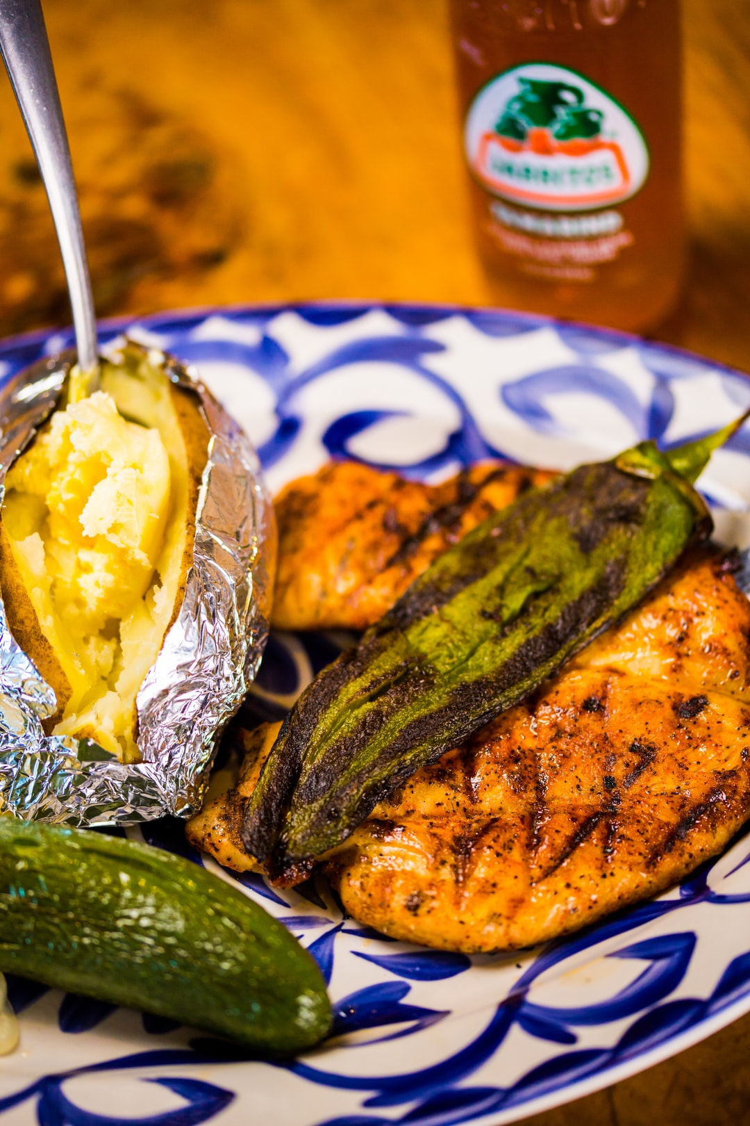 Grilled chicken a la Mexicana with a baked potato, a roasted green chile, a roasted jalapeño and an all-natural-flavored Jarritos Tamarind Mexican Soda. The dish is served on a traditional Talavera plate.