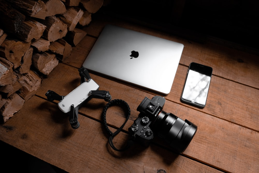 black dslr camera on brown wooden table