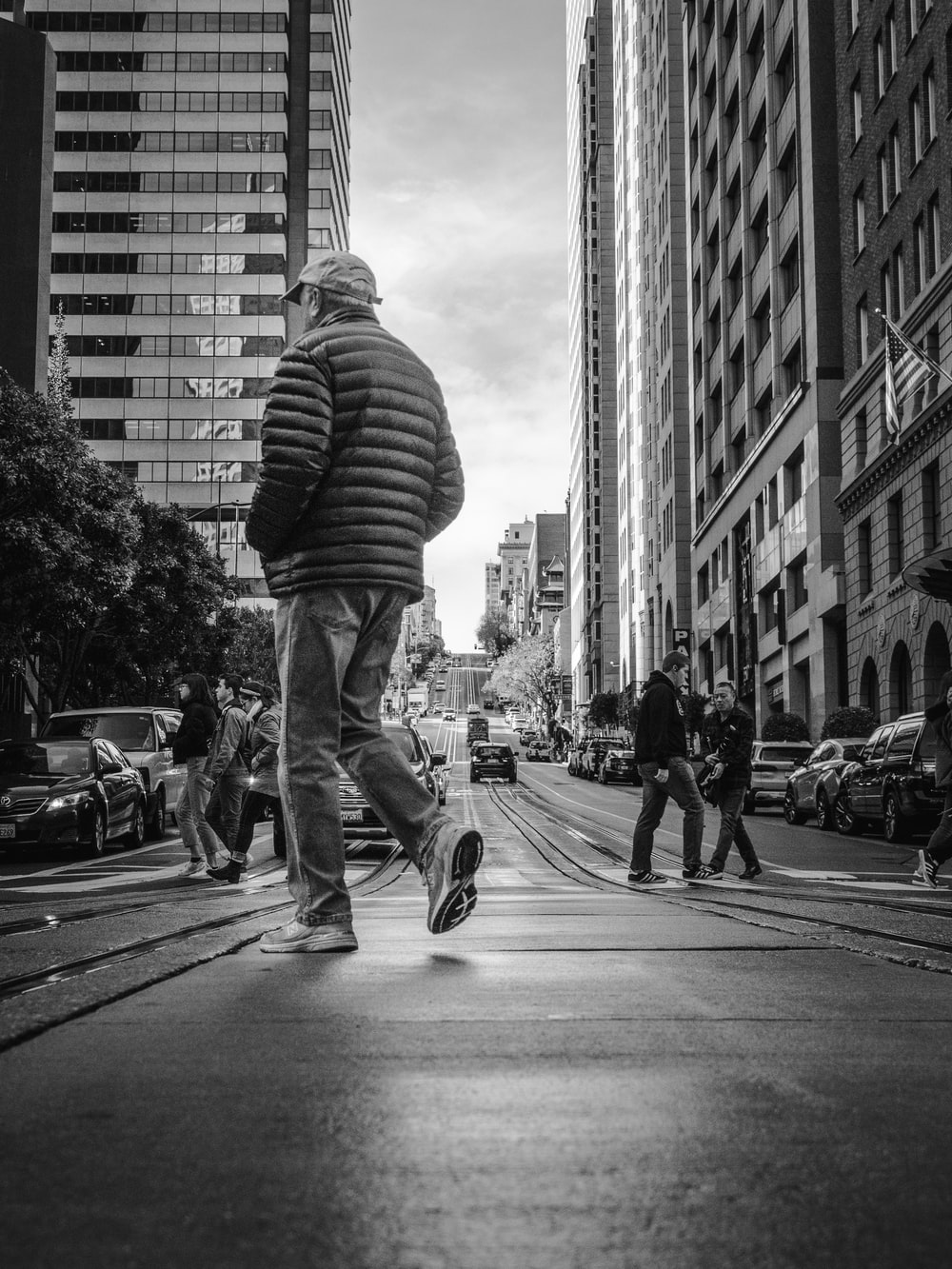 grayscale photo of man in striped shirt and denim jeans walking on street