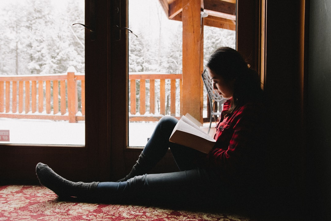 Woman Reading Her Bible In A Snowy Cabin - unsplash