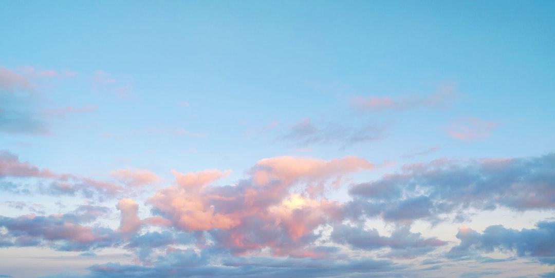 Pink, blue, and yellow clouds against a clear, blue sky at sunset.