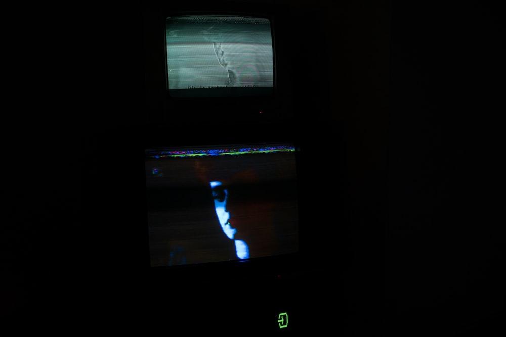 black flat screen tv turned on displaying man in black suit