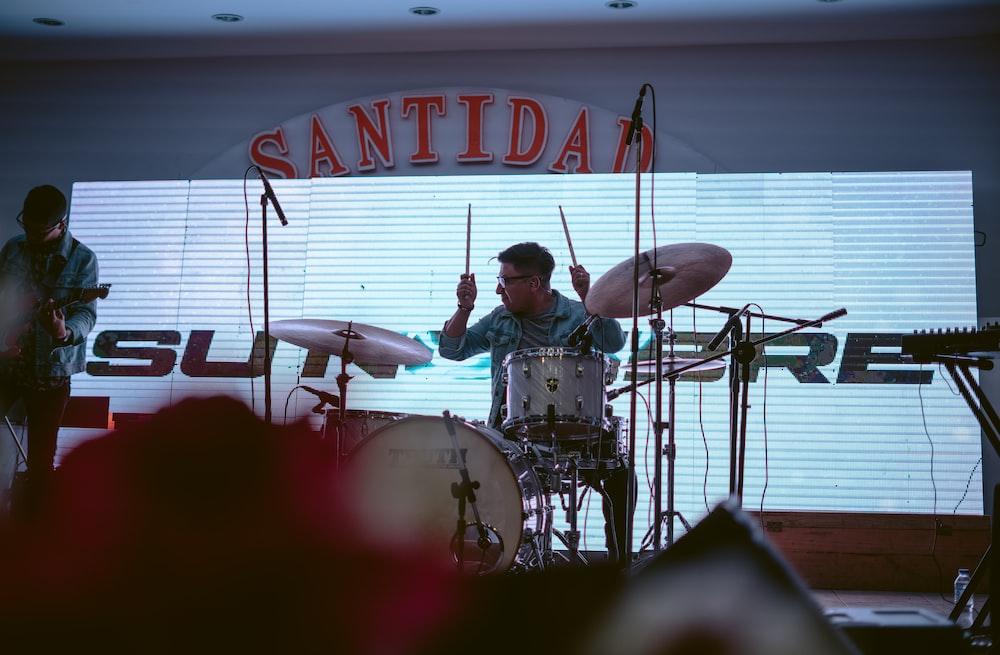 man in gray shirt playing drum