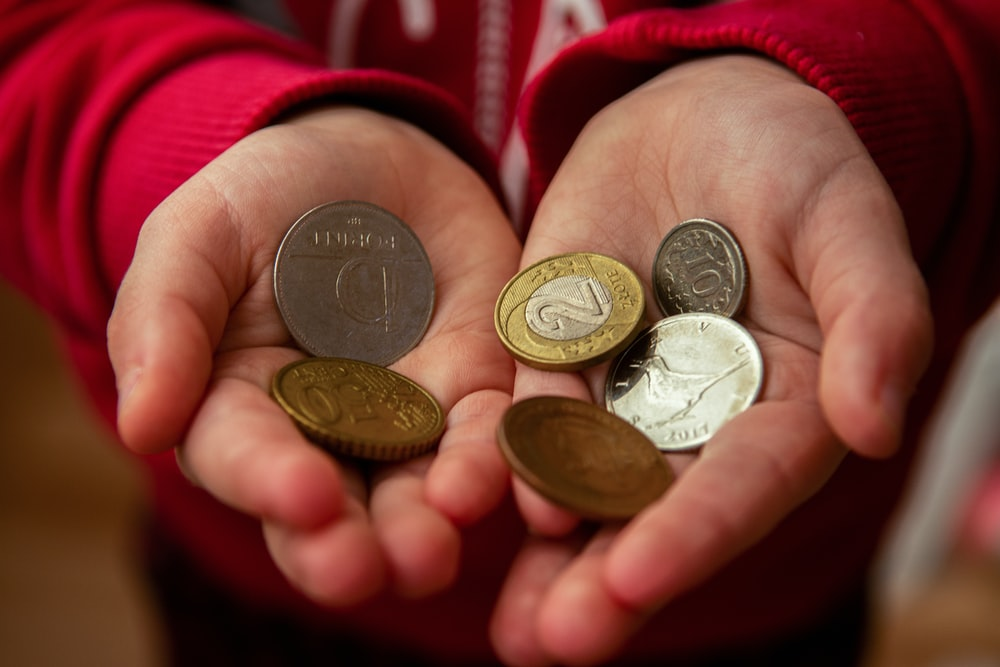 person holding gold round coins