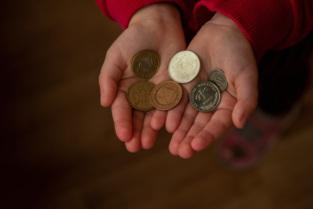person holding silver round coins