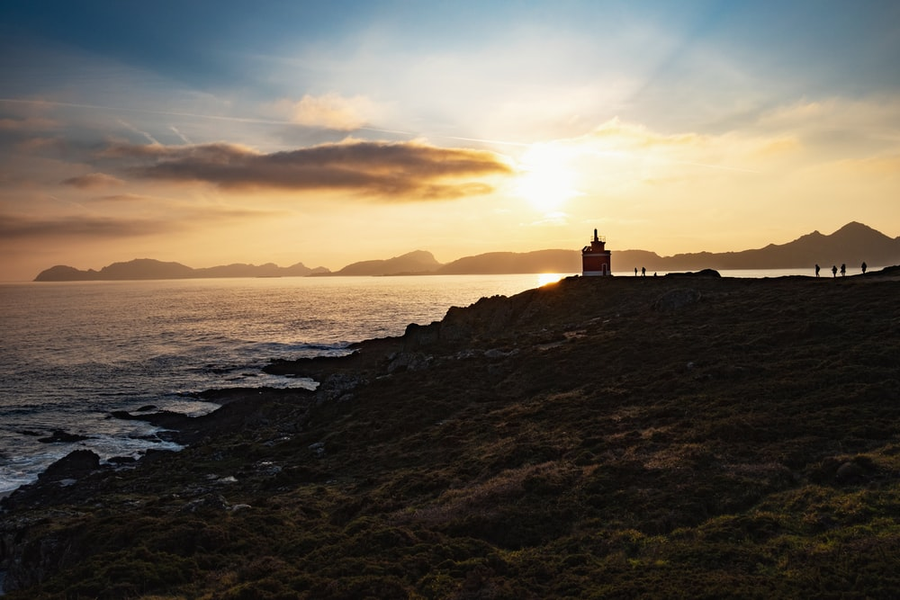 silhouette of lighthouse near body of water during sunset