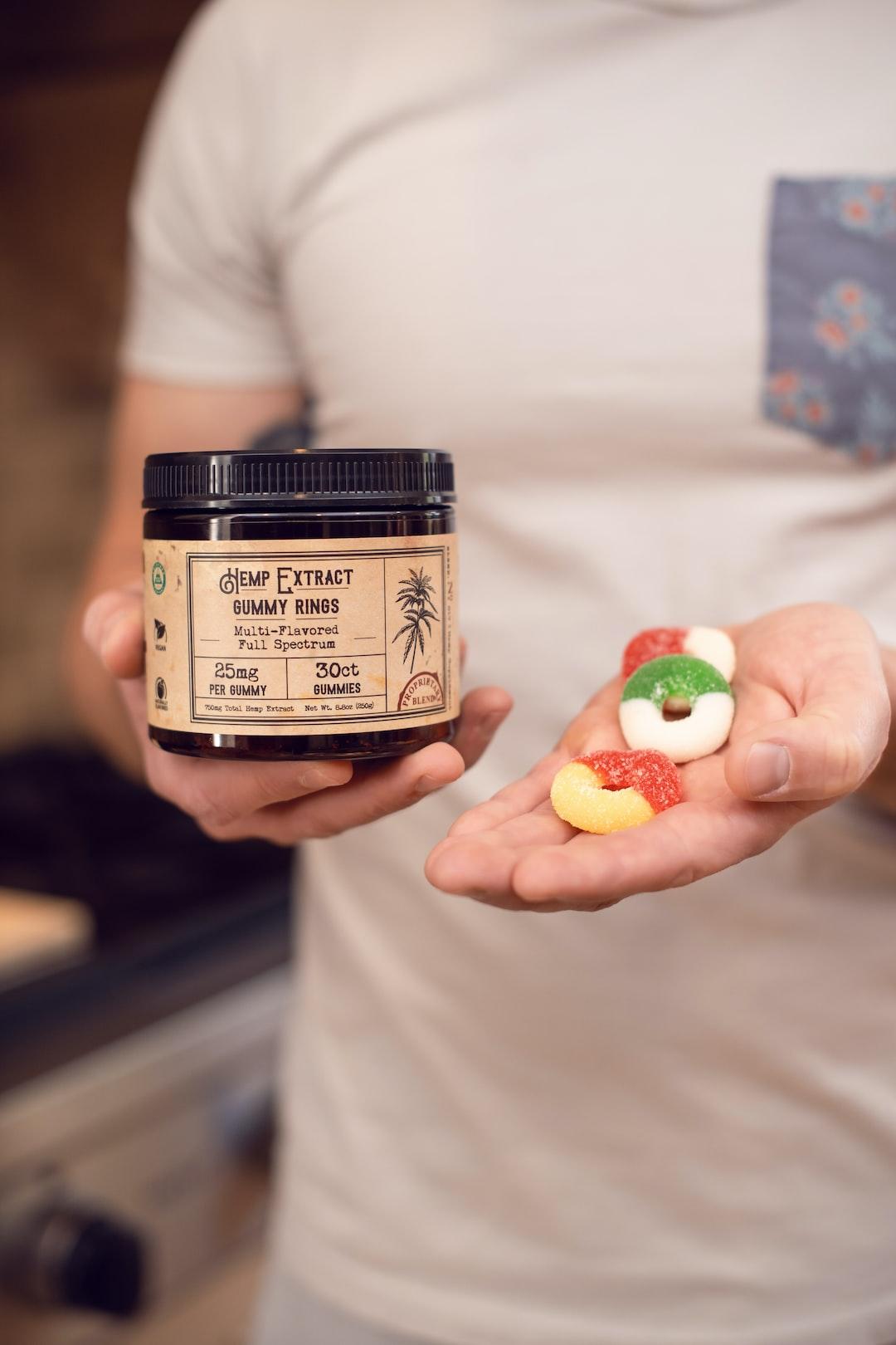 Colorado man holding jar of hemp extract gummies edible candy