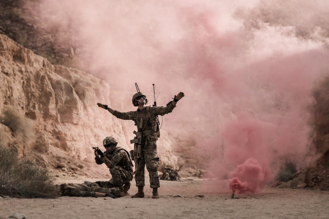 Man In Black and Brown Camouflage Uniform Holding Red Smoke - unsplash