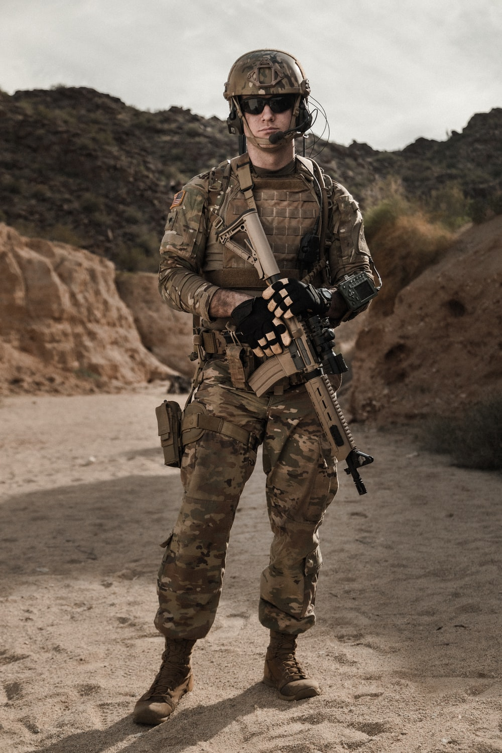 man in brown and black camouflage uniform holding rifle