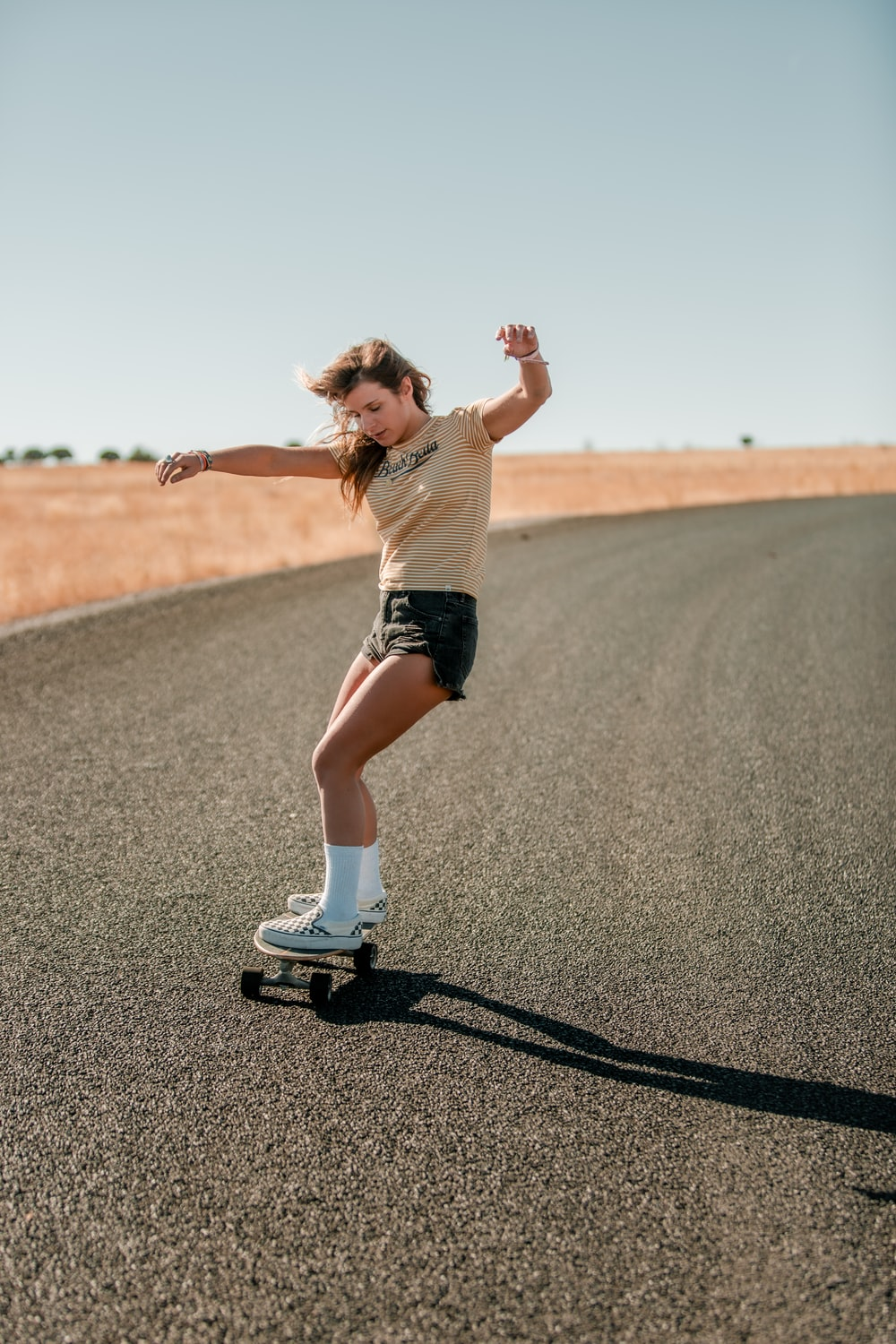 woman in white shirt and black shorts running on road during daytime