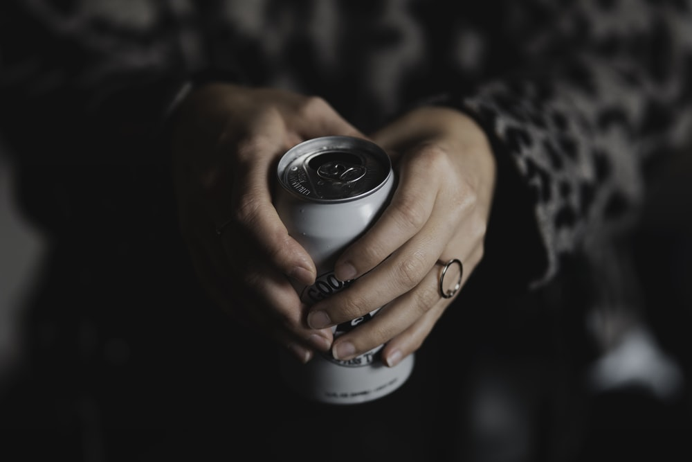 person holding black and silver round container