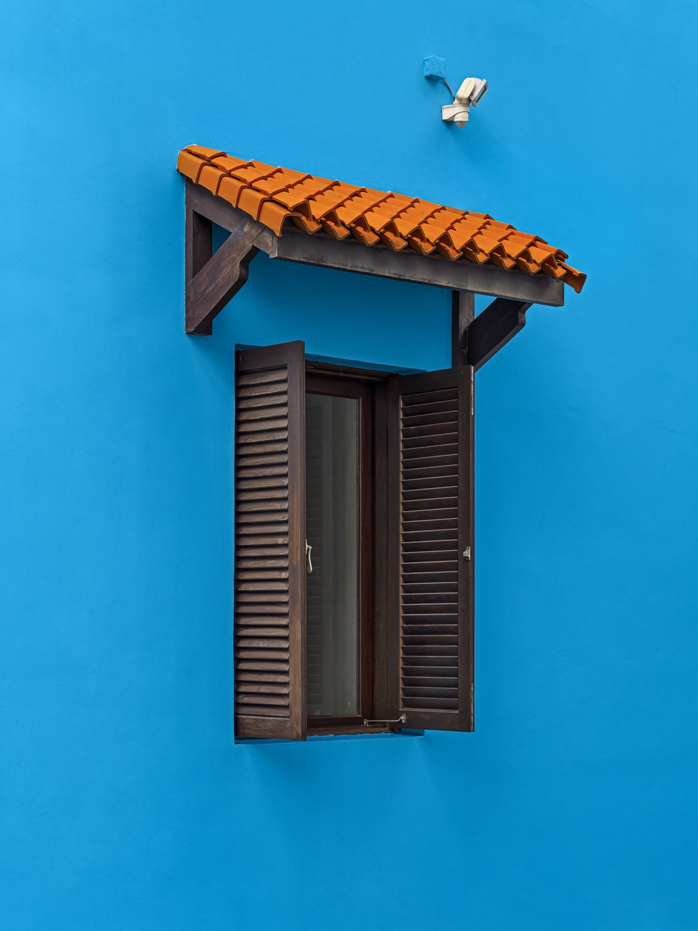 brown wooden window frame on blue wall