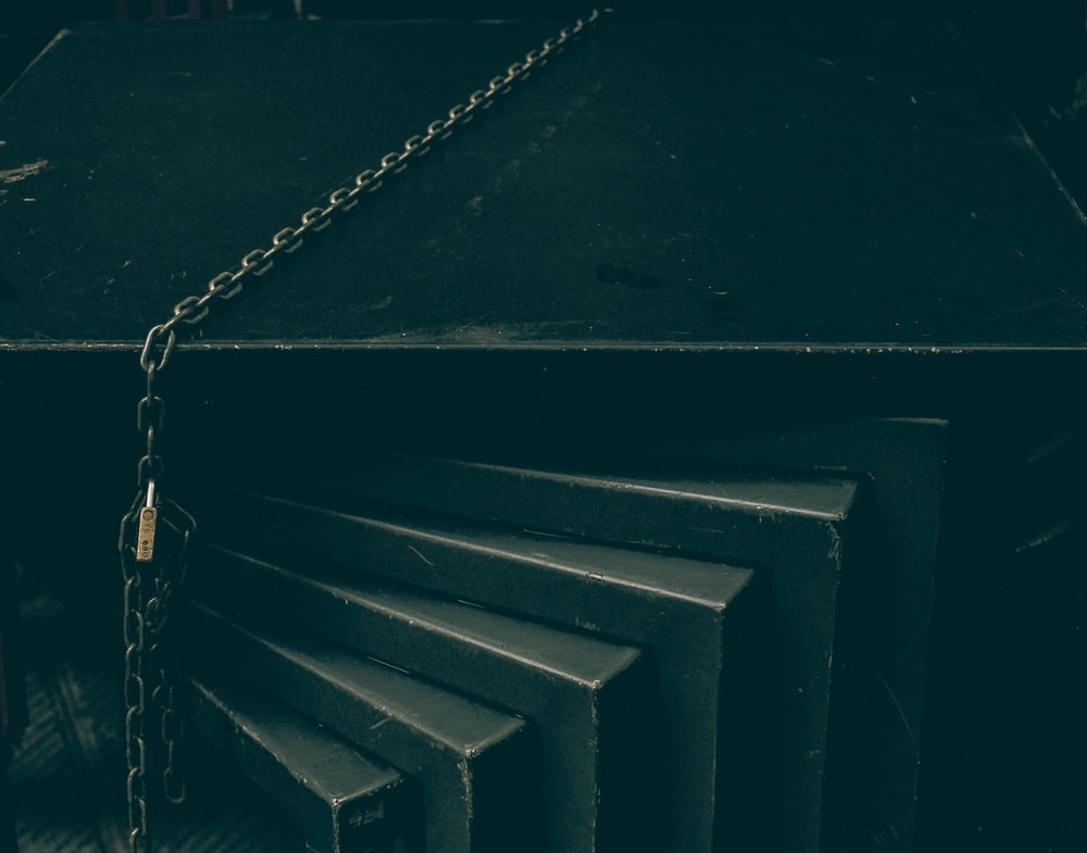 silver chain on black wooden stairs