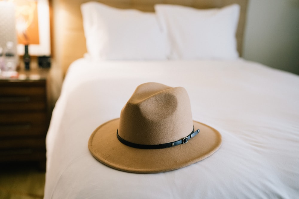brown fedora hat on white bed