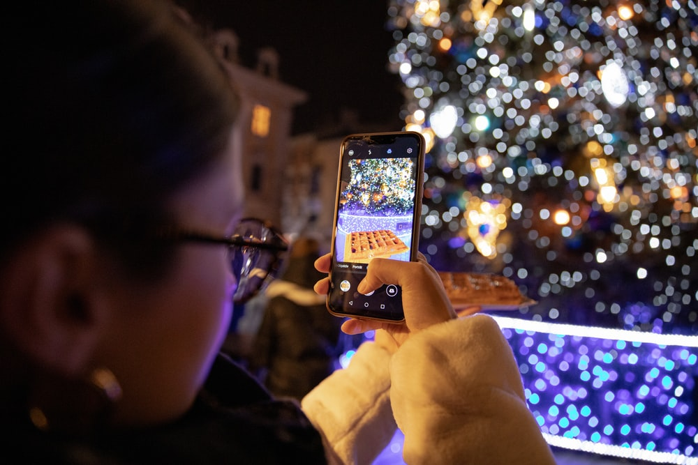 person holding iphone taking photo of lighted christmas tree