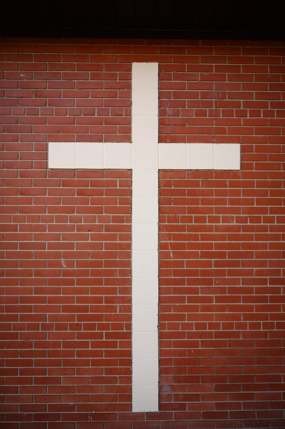 white cross on brown brick wall