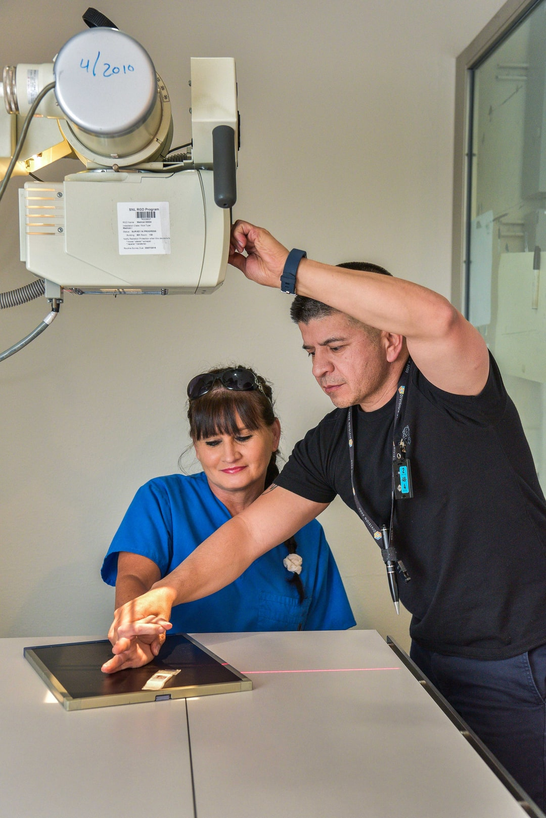 X-ray camera is aimed on hand at Sandia's onsite medical facility.