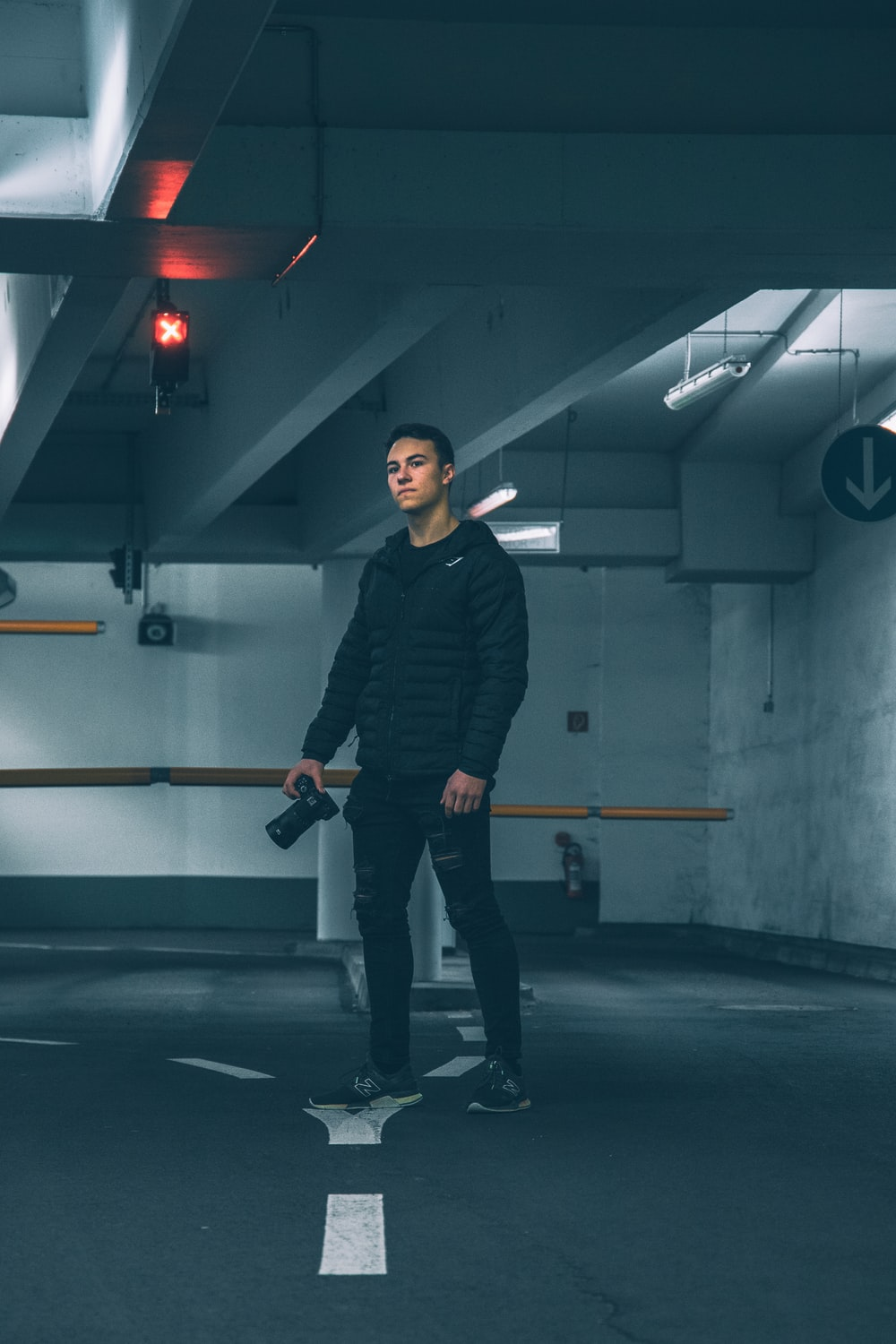 man in black jacket and black pants holding black and gray exercise equipment